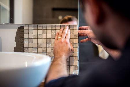 Fabrieksarbeider die mozaïektegels toepassen in badkamersmuren Stockfoto