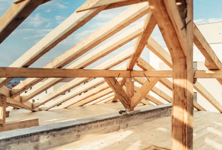Architectural details of inside of attic, wooden roof system at construction site