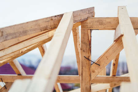 Details of construction site, timber structure of truss roof system. The wooden structure of the building