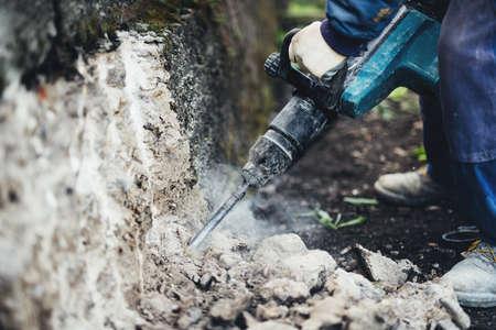 Details van de industriële werknemer. Mannelijke arbeider met behulp van jackhammer pneumatische boormachines