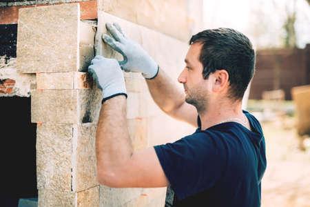 mannelijke metselaar werknemer stenen tegels op huis gevel installeren. Bouw details werknemer Stockfoto