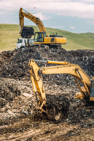 Close up of heavy duty excavators loading dumper trucks with garbage and urban trash