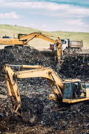 Heavy duty industrial machinery, excavators digging and loading dumper trucks