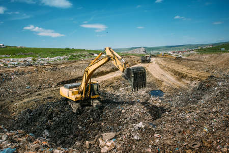 resolving: Excavator loader, bulldozer working in garbage dump. Recycling and resolving environmental issues