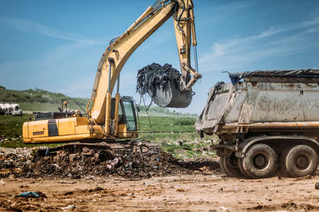 Industrial excavator using scoop and moving earth and trash at garbage dumping site. Stock Photo