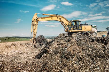 industrial works with excavator using heavy duty scoop at garbage dumpsite
