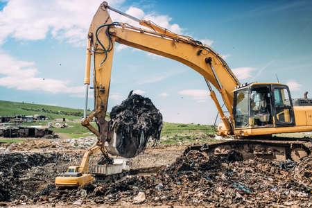 scrapyard: Industrial excavators and heavy duty machinery working on garbage dump site.