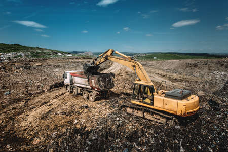 Industrial excavator loading dumper trucks with garbage Stock Photo