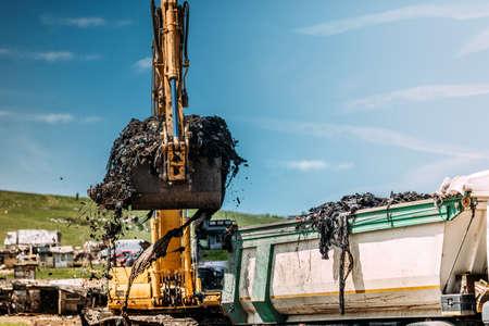 Industrial excavator loading dumper trucks with garbage on site