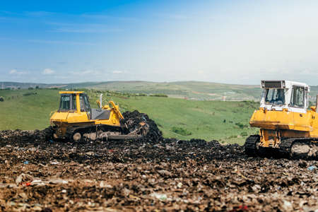 Industrial bulldozers working on construction site. Details of wasteland, garbage disposal dumping grounds