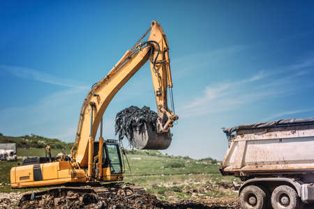 Industrial bulldozer and excavator working on site.  Stock Photo