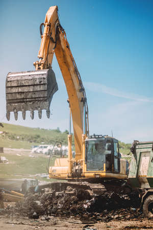 details of heavy duty machinery working on site. Excavator loading dumper trucks