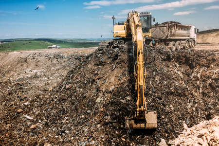 Urban city waste dumping grounds with excavator loading trucks