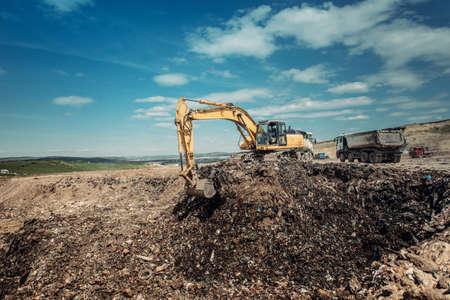scrapyard: industrial garbage dumpsite - excavation works with heavy duty machinery