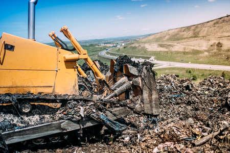 Industrial bulldozer working on garbage dumping site