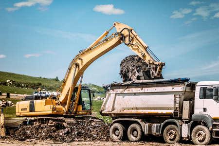 Industrial excavator loading dumper trucks at garbage dumping site Stock Photo