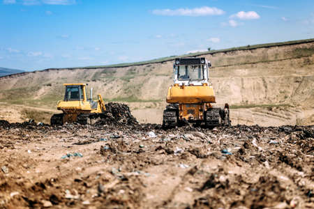 Yellow mini bulldozers working and moving garbage on dumping site