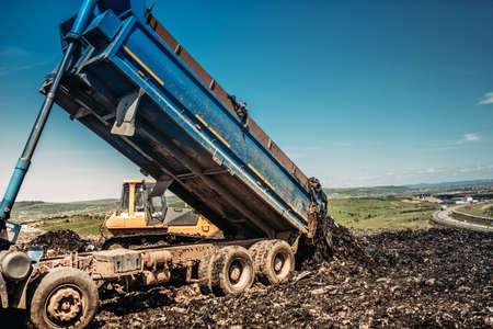 industrial dumper trucks unloading garbage into trash hill