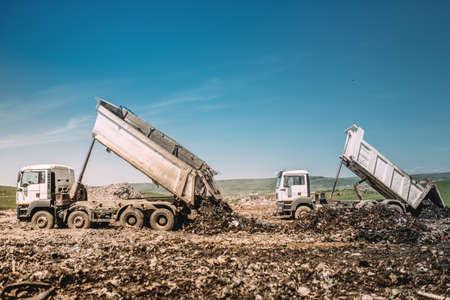 Industrial heavy duty dumper trucks unloading at construction site Banque d'images