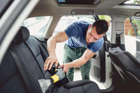 プロの仕事を掃除機をかけると、自動車を洗浄します。車のケアと詳細設定の概念