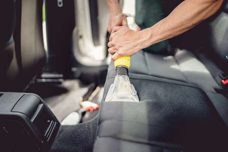 Car detailing and car care concept - Professional using steam vacuum for draining stains