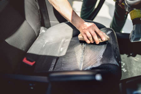 Car care concept, detailing and cleaning details. Worker using cleansing techonology for upholstery