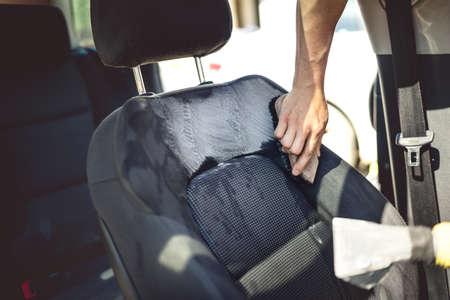 Autoverzorgingconcept - detaillering van bestuurderszetel die professionele hulpmiddelen en reinigingsmachines gebruiken