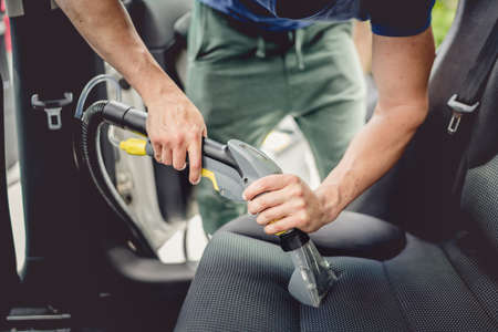 waxes: Details of car cleaning - male using professional steam vacuum for dirty car interior