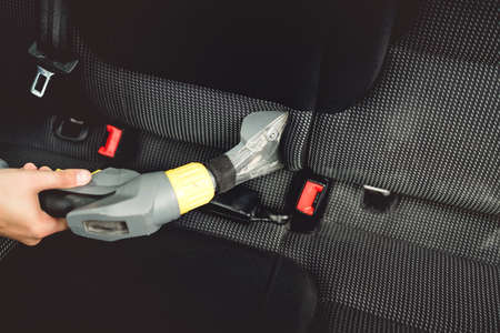 waxes: Close up details of car worker, vacuuming upholstery seats with steam cleaner Stock Photo
