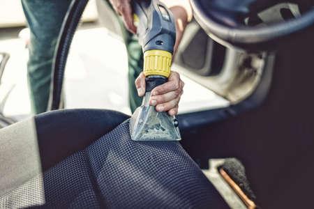 waxes: Close up details of car steats vacuuming using steaming tools