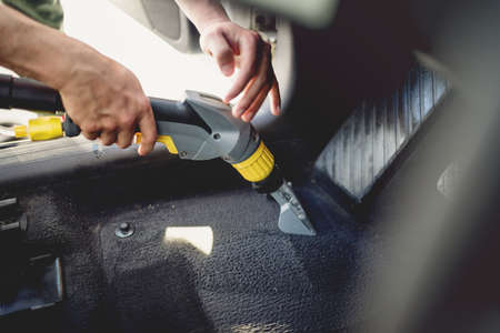 Professional detailer vacuuming carpet of car interior, using steam vacuum