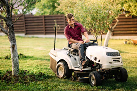 seeding: male worker using lawmower for landscaping works. Motorised agriculture concept