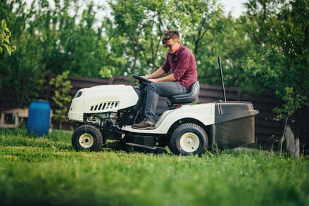 seeding: Worker using lawn mower for cutting grass in garden Stock Photo