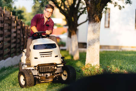 seeding: Portrait of man using lawn tractor and cutting grass in garden during weekend time Stock Photo
