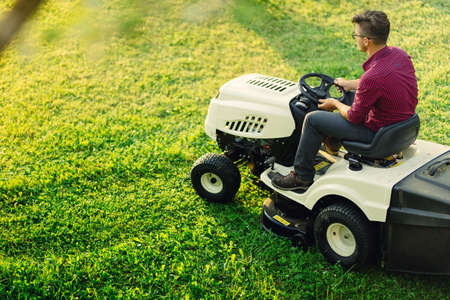 seeding: Gardening works with young male cutting grass. Industrial lawn mower in action