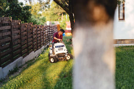 male worker riding lawn mower and trimming grass in garden Stock Photo