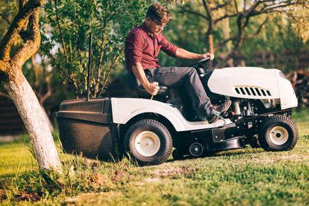 paysagiste: Paysagiste professionnel utilisant la tondeuse à gazon pour couper l'herbe dans le jardin