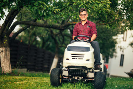 seeding: Lawncare concept - Smiling worker using ride on grass mower Stock Photo