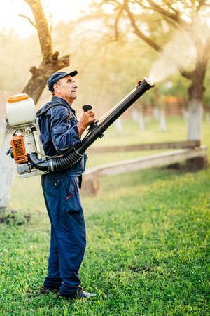 Industrial farm worker gardening and spraying pesticide