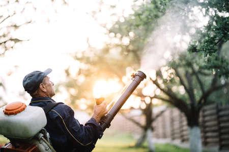 농부, 유기 농약을 분무하기위한 배낭 기계를 사용하는 열심히 일하는 재주꾼