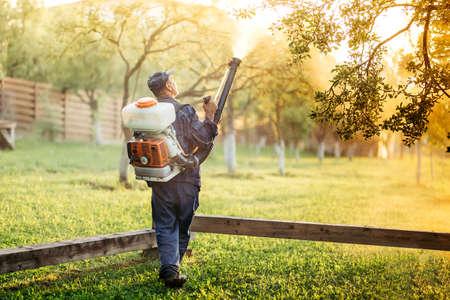 Industriële werknemer die spray gebruikt voor organische bestrijding van pesticiden in fruitboord