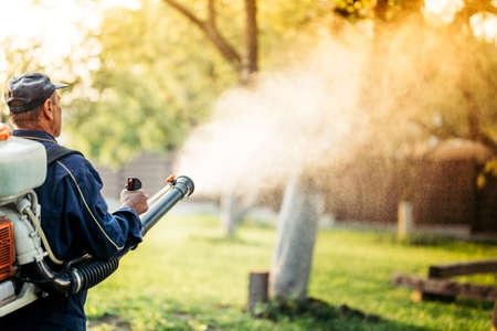 Landbouwdetails met landbouwer die spuittoestelmachine voor pesticidecontrole in fruitboomgaard met behulp van tijdens zonsondergangtijd