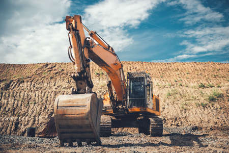 heavy: Industrial heavy duty excavator on highway construction site, bucket details, dirt and gravel all around Stock Photo