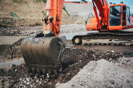 moving truck: Close up of excavator scoop in dirt, working on highway construction and building foundation