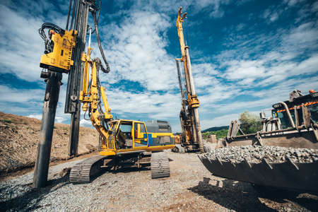 Highway construction site with heavy duty machinery. Two Rotary drills, bulldozer and excavator working Stock Photo