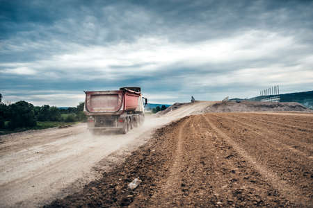 Industrial dumper trucks working on highway construction site, loading and unloading gravel and earth. heavy duty machinery activity