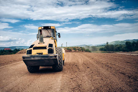 Vibratory Soil Compactor during highway building. Industrial roadworks with heavy-duty machinery Stock Photo
