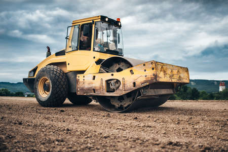 construction vibroroller: close up details of highway construction site - industrial machinery, vibratory soil compactor  working Stock Photo