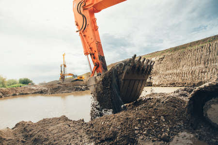moving truck: Highway construction works with details of excavator scoop loading earth and soil