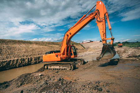 Heavy duty excavator machinery working in highway construction site. Building viaduct and digging with excavator Stock Photo